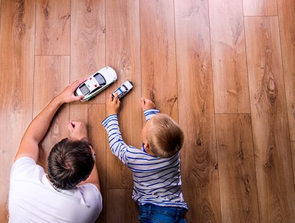 Dad and son playing on floor | Andy's 5 Star Flooring